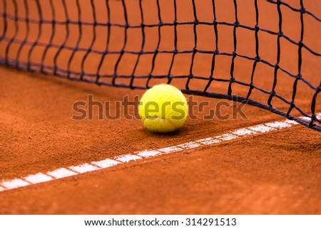 tennis ball on a clay court, close to the net