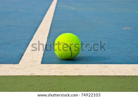 Tennis ball on blue court - stock photo