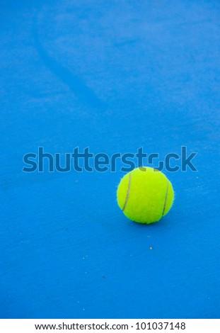 tennis ball on blue hard court - stock photo