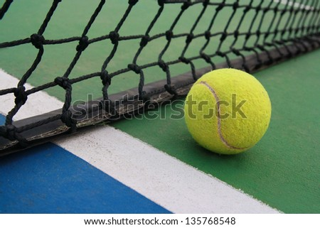 tennis ball on green blue court and net in sport competition background, sport club
