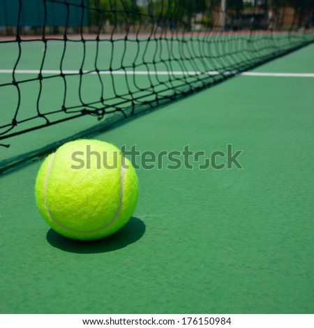 tennis ball on green old court - stock photo
