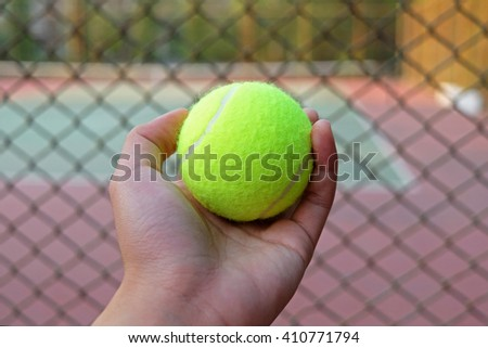 tennis ball on hand blur background court