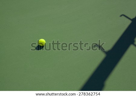 tennis ball on hard court with copy space - stock photo