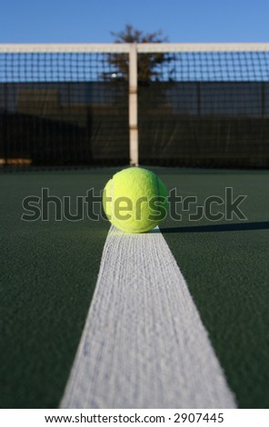 Tennis ball on line with net background