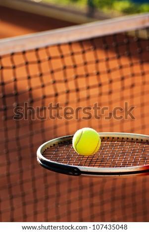 tennis ball on racket near net - stock photo