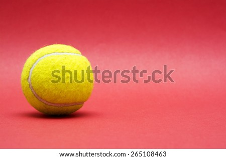 Tennis ball on red background with copy space.