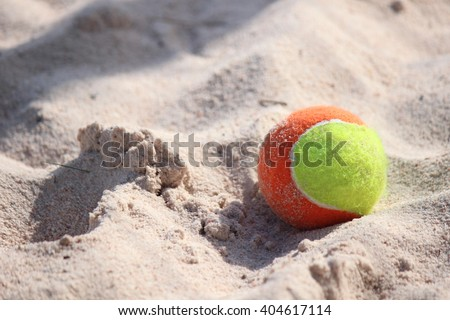 Tennis ball on the beach - stock photo