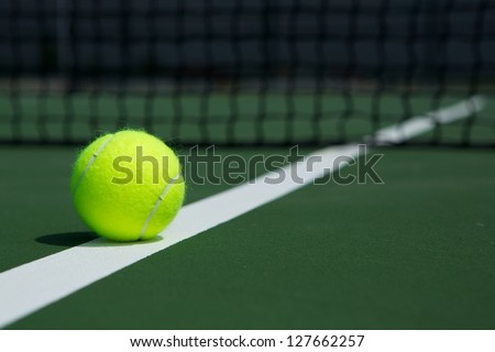 Tennis Ball on the Court Close up with Net in the Background