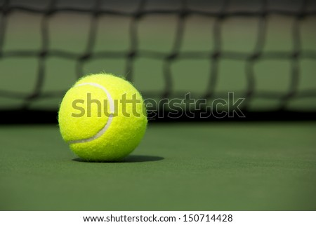 Tennis Ball on the Court Close up with the Net Beyond - stock photo