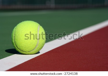 Tennis ball on the court line diagonal