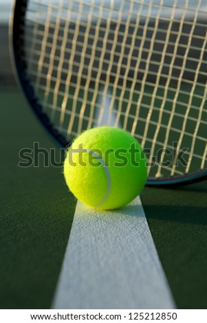 Tennis Ball on the Court Line with the Racket Beyond - stock photo