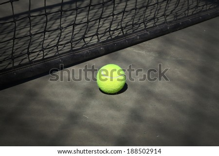 Tennis ball on the court with the net on the background - stock photo