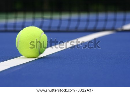 Tennis ball on the line of a blue court - stock photo