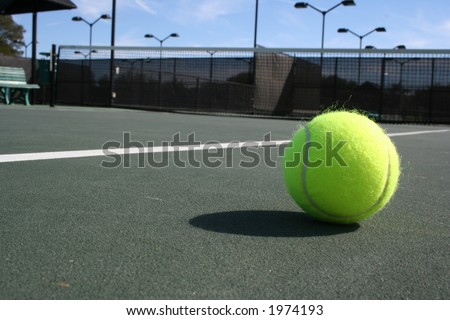 Tennis ball with net in background