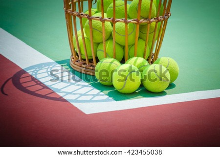 Tennis Ball with Racket on old basket tennis court - stock photo