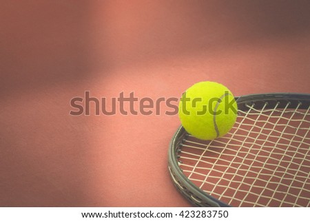 Tennis Ball with Racket on the clay tennis court. vintage - stock photo