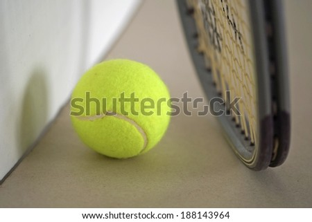 Tennis ball with racket on the ground.