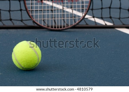 Tennis ball, with racquet and tennis net in background