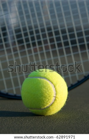 Tennis Ball with the racket in the background