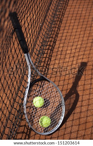 Tennis balls and rocket on court field in sunny day - stock photo
