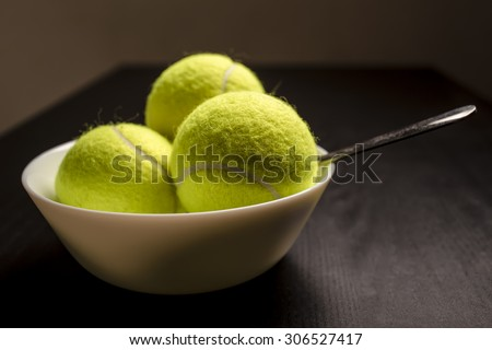 Tennis balls are in a bowl instead of ice cream, symbolizing changes and refusal of desserts and sweet and replacement of sports and healthy lifestyle. Dark version.