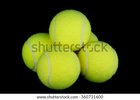Tennis balls isolated against a black background - stock photo