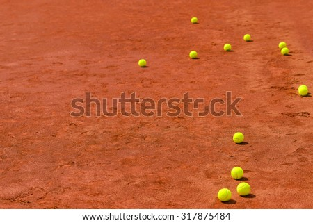 Tennis balls on clay court with copy space as sports background, selective focus - stock photo