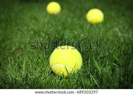 Tennis balls on fresh green grass outdoors