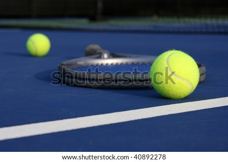 Tennis balls on the court with a racket - stock photo