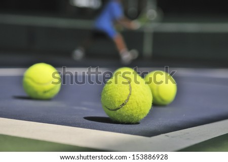 Tennis balls on the court with player and net background