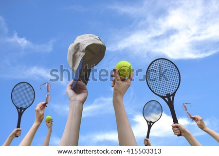 Tennis balls, sunglasses, racket, cap in hand. Blue sky background. Concept: friendship, relaxation, sports, summer. Good relax with friends.Sport is a useful and fun.