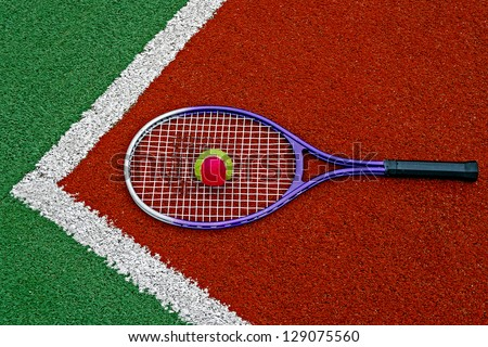 Tennis colored ball and racket, placed in the corner of a synthetic field. - stock photo