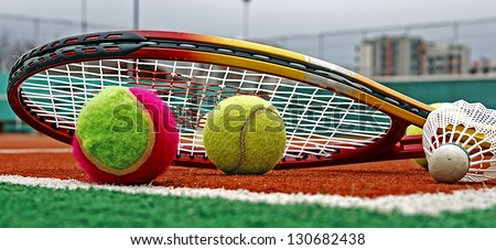 Tennis colored balls, badminton shuttlecocks and rackets, placed in the corner of a synthetic field.