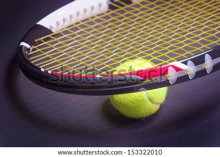 Tennis Concepts: Tennis Racket with Tennis Ball on Black background. Horizontal image - stock photo