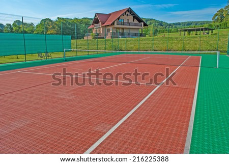 Tennis court, a beautiful chalet in the back and surrounded by trees and hills. The perfect place for relaxation and exercise for a good health - stock photo