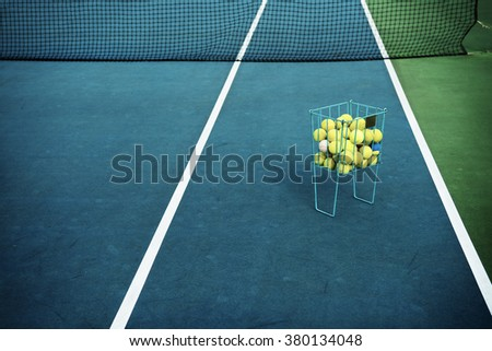 Tennis court with tennis balls in tennis ball basket stand. Intentionally shot in surreal tone. - stock photo