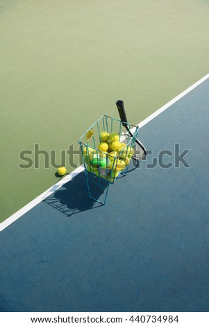 Tennis court with tennis balls in tennis ball basket stand with natural shadows. Intentionally shot in surreal tone. - stock photo