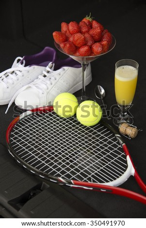 Tennis equipment and strawberries with a glass of fizz - stock photo