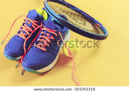 Tennis equipment on yellow background