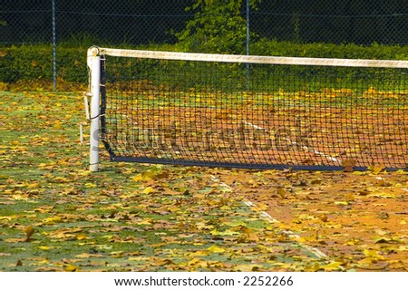 Tennis field covered by fallen autumn leafs - stock photo