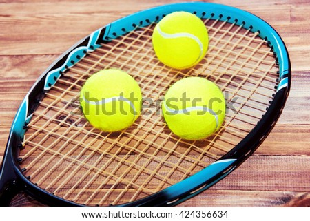 Tennis game. Tennis ball and racket on wooden background. Vintage retro picture. - stock photo