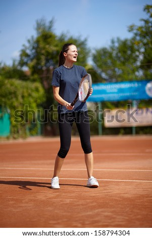 Tennis instructor teaching on a clay court - stock photo