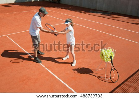 Tennis instructor with young talent on clay court