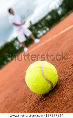 Tennis match at a clay court with a ball lying on the side