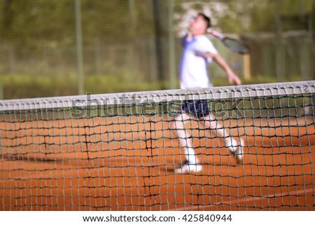 Tennis net, Man plays tennis, blurred motion - stock photo