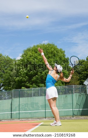 Tennis player about to serve on a sunny day