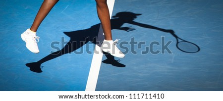 Tennis player and shadow - stock photo
