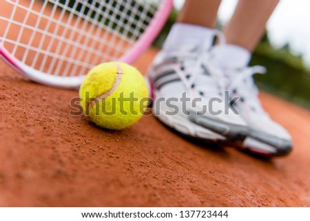 Tennis player at the court with racket and a ball - stock photo