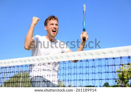 Tennis player celebrating victory. Winning cheering man happy in celebration of success and win. Fit male athlete winner on tennis court outdoors holding tennis racket in triumph by the net. - stock photo