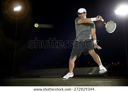Tennis player during a night match with dark background - stock photo